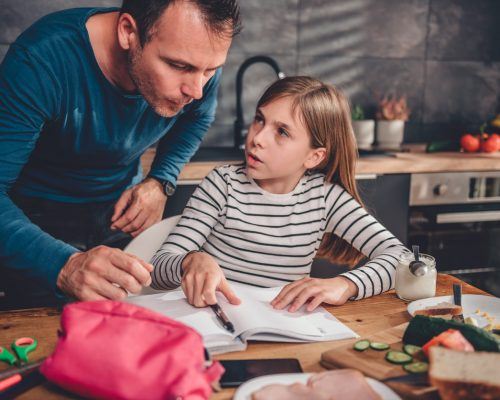 Father helping daughter with homework on a dining table in kitchen