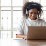 African businesswoman wearing headphones using laptop at work typing message