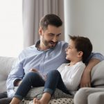 Little son having confidence conversation with father at home